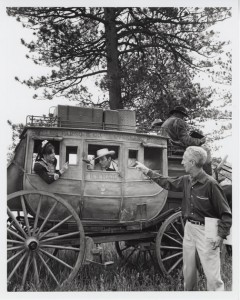 """Norman Rockwell with actors Mike Connors and Stephanie Powers on the set of """"Stagecoach."""""""