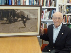 "Ralph H. Baer poses in Norman Rockwell Museum's Archives, September 2011, with a painting of another pioneer: Daniel Boone. Mr Baer is considered the ""father of video games,"" and donated the original painting to the Museum back in the 1990s. Photo courtesy Ralph H. Baer. All rights reserved."