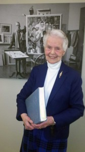 "Norman Rockwell researcher Priscilla Anthony holding a copy of ""Norman Rockwell: A Definitive Catalogue."" Anthony helped to type and deliver the final manuscript of this comprehensive catalogue of Rockwell's work. Photo by Norman Rockwell Museum. All rights reserved."