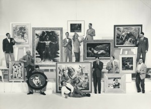 """Group photo of Famous Artists School Faculty. Left to right: Harold von Schmidt, John Atherton, Al Parker, founder Al Dorne (white shirt, on ground), Norman Rockwell (with painting created for Cecil B. DeMille's 1949 film, """"Samson and Delilah""""), Ben Stahl, Peter Helck, Stevan Dohanos, Jon Whitcomb, Austin Briggs (rear, far right), and Robert Fawcett (front, far right). ©Norman Rockwell Museum Archives, gift of Famous Artists School. All rights reserved."""