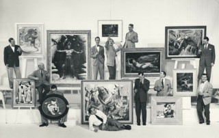 "Group photo of Famous Artists School Faculty. Left to right: Harold von Schmidt, John Atherton, Al Parker, founder Al Dorne (white shirt, on ground), Norman Rockwell (with painting created for Cecil B. DeMille's 1949 film, ""Samson and Delilah""), Ben Stahl, Peter Helck, Stevan Dohanos, Jon Whitcomb, Austin Briggs (rear, far right), and Robert Fawcett (front, far right). ©Norman Rockwell Museum Archives, gift of Famous Artists School. All rights reserved."